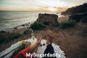 En la imagen se ven los pies de una pareja al borde de la costa en una colina. Observan el atardecer y disfrutan de un trago. Compartir tiempo es muy importante para una relación. Por eso, regalar esto seria el regalo adecuado.