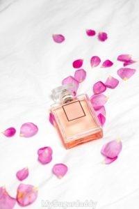 Vemos un frasco de perfume tirado sobre la cama con petalos de rosas. Muy feminino y muy atento.