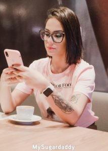 En la imagen se ve una chica joven como utiliza su dispositivo móvil. Es muy bella y esta bien concentrada. En estos dispositivos se encuentra toda la información que se necesita para hacer un obsequio.