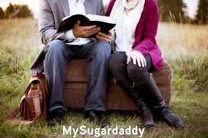 La foto esta centrada en dos personas. Se ven sus cuerpos pero no sus caras. El hombre sostiene un libro y le muestra algo a la mujer. Que serio es este encuentro. Sentados en un sillon a las afueras.