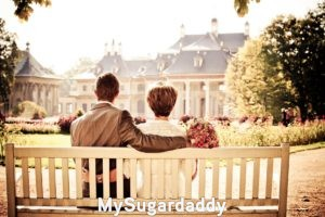 Podemos ver a una pareja que disfruta de un dia en el jardin. Estan sentados sobre un banco y se sotienen ambos. Observan una casa, seguramente, la de ellos. Es la personalidad de coquetear tradicional, ya que visten y parecen ser de la vieja escuela.