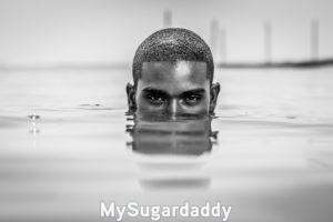 Se puede ver a un hombre sumergido en el agua hasta los ojos. Tiene una mirada seductora y profunda. La imagen esta en blanco y negro. Pelo corto y cejas negras. Parece tener una fuerte personalidad para coquetear.