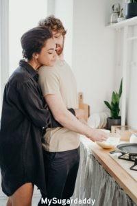 Relación nueva: Podemos ver a una mujer abrazando de espaldas a un hombre. El esta levemente girado hacia atrás y la mira. Parece que él le esta haciendo el desayuno.