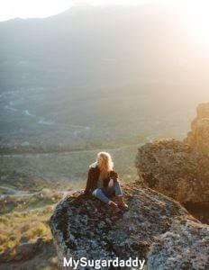 Relación nueva: Ser soltera significa ser libre de cualquier cosa. Tiempo para si misma. La foto muestra exactamente eso. Una mujer sobre una roca disfrutando el paisaje eterno. Sin preocupaciones y libre.
